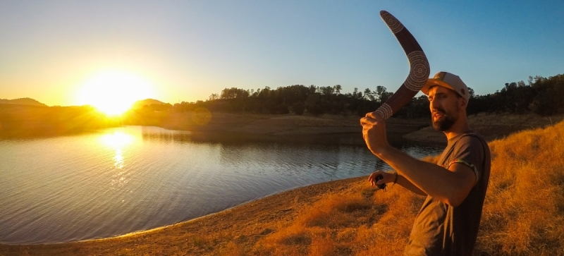 Man with boomerang in hand near lake at sunset