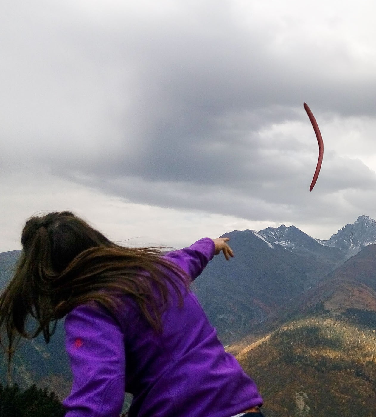 Girl, throw a boomerang, mountains