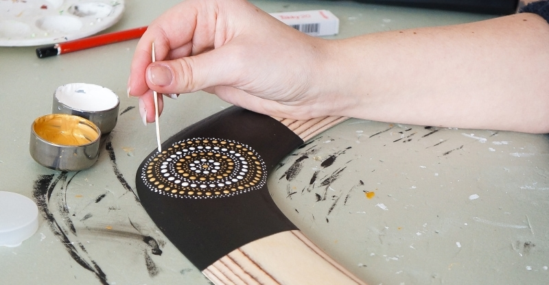 women is painting dots on the wooden boomerang